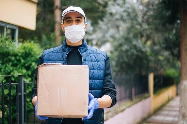 Repartidor entrega paquete protegiéndose de la COVID-19