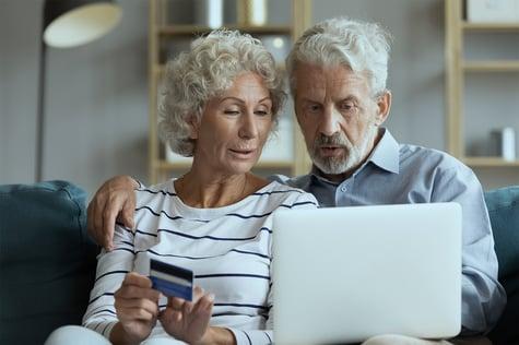 viejitos en la computadora con una tarjeta de credito