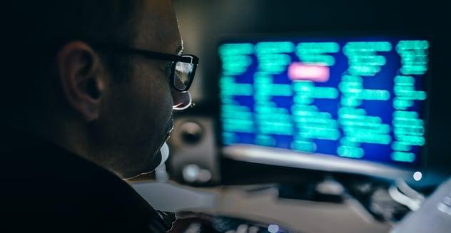 hombre mirando datos en una computadora