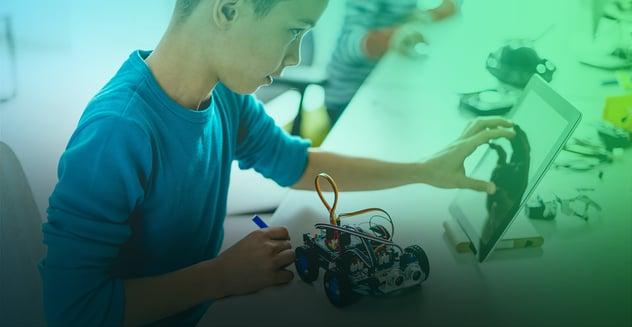 joven programando robot a través de una tablet