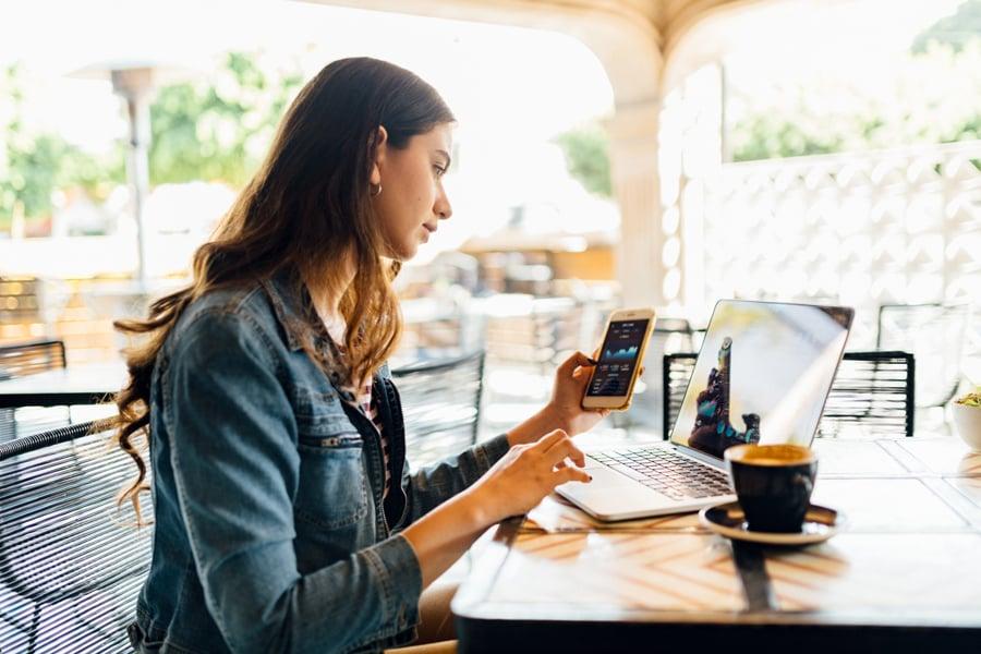 mujer conectada a internet desde smartphone y laptop
